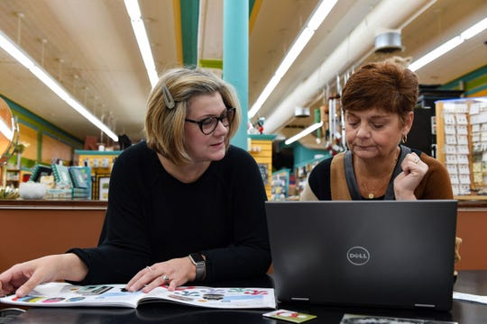 Jamie Scarbrough and Pam Boyum look over catalogs for purchasing new inventory at Zandbroz Variety on Tuesday, October 29, in Sioux Falls.
