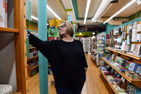 Jamie Scarbrough adjusts a display as she walks past in Zandbroz Variety on Tuesday, October 29, in Sioux Falls.