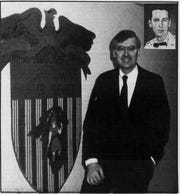 Then Gov. Gerald Baliles stands next to the seal of Fishburne Military School in June 1987 during a visit to his alma mater with his class photo inset.
