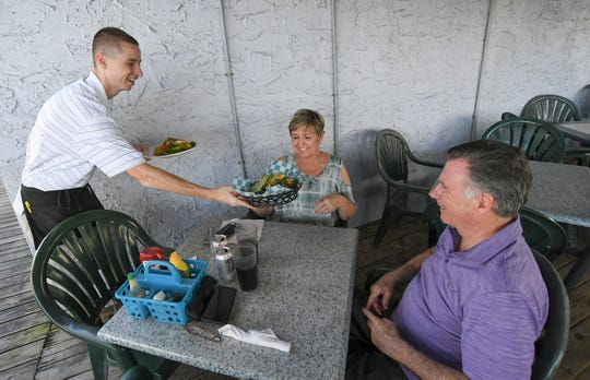 "Brandon Jasuta (left), server at the Pelican Cafe, serves up lunch to first-time customers Judy and Paul Silliman, of Port St. Lucie, at the cafe's outside deck on Tuesday, Oct. 29, 2019, in Stuart. ""We want them to stay and I think they deserve a break,"" Paul Silliman said."
