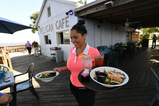 "Chantel Hazell, manager of the Pelican Cafe, carries two servings of Krueger Creek salads for diners on Tuesday, Oct. 29, 2019, at the popular riverside cafe that overlooks the St. Lucie River in Stuart. The owners of the cafe, Paul and Linda Daly, were granted a new 10-year lease with the option of two five-year extensions for the cafe after a battle with the Stuart City Commission. ""It feels great, now we won't have to be out of a job,"" Hazell said. ""We were afraid of having to get new jobs in two years."" The Dalys now plan to build an addition to the cafe, with added seating."