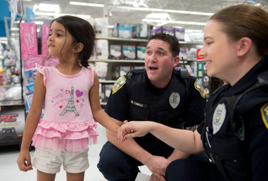 Jada Moore, 4, of Port St. Lucie, surveys the toy department with Port St. Lucie Police Officers Michael Cimino and Ariel Dennis during the department's annual Shop with a Cop event Wednesday, Dec. 14, 2016, at the Walmart in Port St. Lucie.