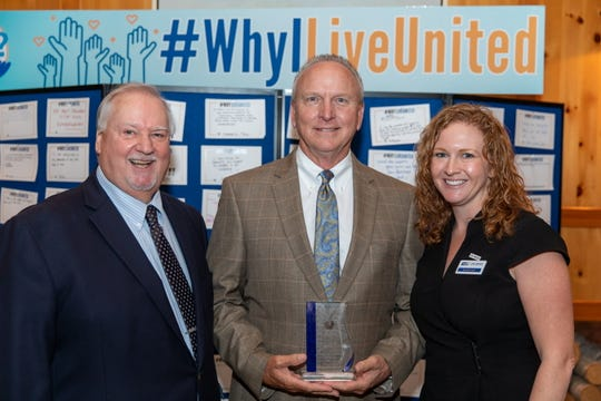Chad Morrison, center, receives the Ralph T. King Lifetime Service Award for his 20 years of work with the United Way from United Way's Michael Kint, left, and Meredith Egan, at the Community Leaders Breakfast on Oct.17, 2019.