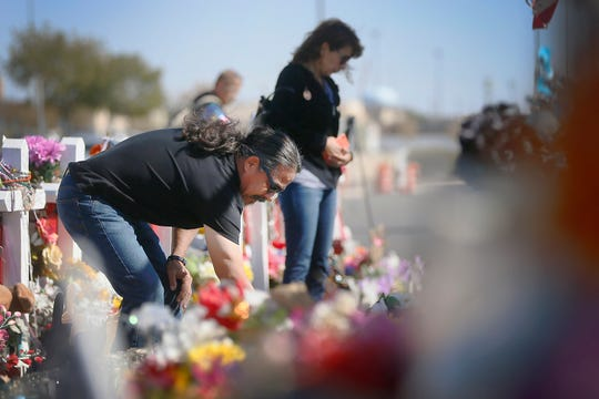 Valentine and Terry Soto pick up vases and flowers that have fallen down at the Walmart memorial site Tuesday, Oct. 29, in El Paso. Valentine said him and Terry like to go to the site every so often to clean up the flowers and fix signs. The memorial was set up after the Aug. 3 shooting at Walmart where 22 people were killed and 25 were injured during the shooting.