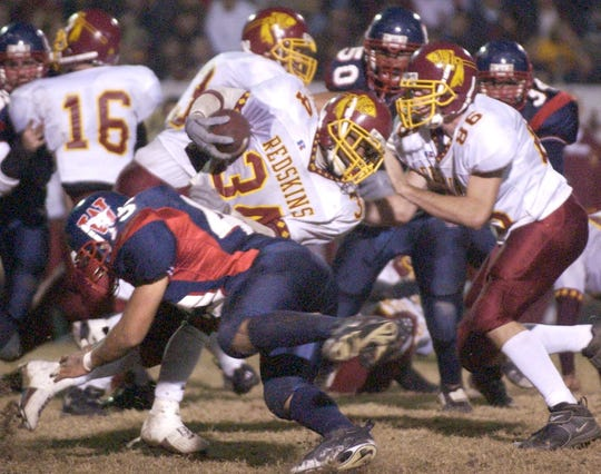 Tulare Union's Daryl Jackson (34) gets tackled by Tulare Western's Kevin Canada (45) during the Victory Bell game at Bob Mathias Stadium.