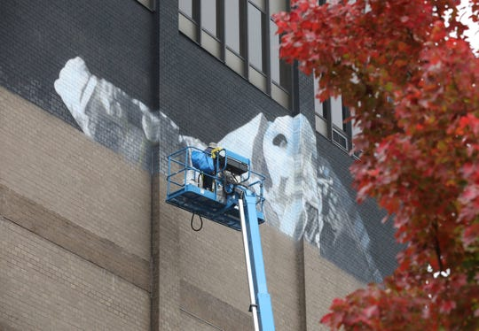 Mural artist Victor Ash at work painting his mural on the side of the Radisson hotel in New Rochelle Oct. 29, 2019.  On Nov. 2, 2019, there will be an Art Walk through the streets of New Rochelle for the premiere of the NRNY Artsy Murals. The art and the  walk were curated by Street Art for Mankind.