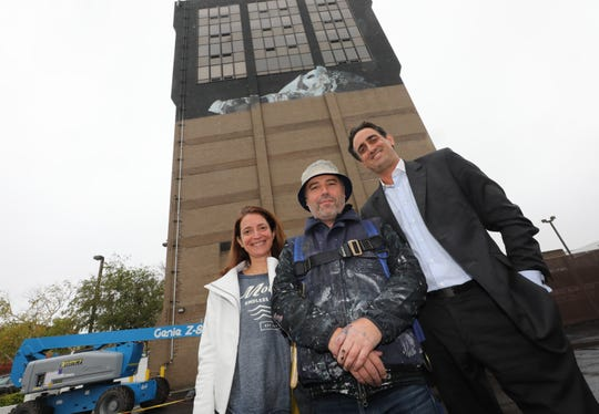 Audrey and Thibault Decker, the co-founders of Street Art for Mankind, flank mural artist Victor Ash who is painting a mural on the side of the Radisson hotel in New Rochelle Oct. 29, 2019.  On Nov. 2, 2019, there will be an Art Walk through the streets of New Rochelle for the premiere of the NRNY Artsy Murals. The art and the  walk were curated by Street Art for Mankind.