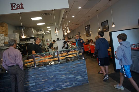Rico DellaMonica, owner of Margherita's Pizza watches customers walk in to the pizzeria's new Newark site in the Park N Shop shopping center on South Main Street.