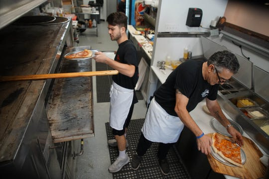 (left to right)Mario DellaMonica, puts a slice of pizza in the oven at Margherita's Pizza while his uncle and owner of Margherita's Rico DellaMonica prepares slices for customers visiting the pizzeria's new new Newark site in the Park N Shop shopping center on South Main Street.