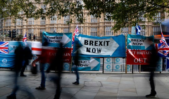 Pedestrians pass Brexit banners opposite parliament in London, on Oct. 29, 2019.