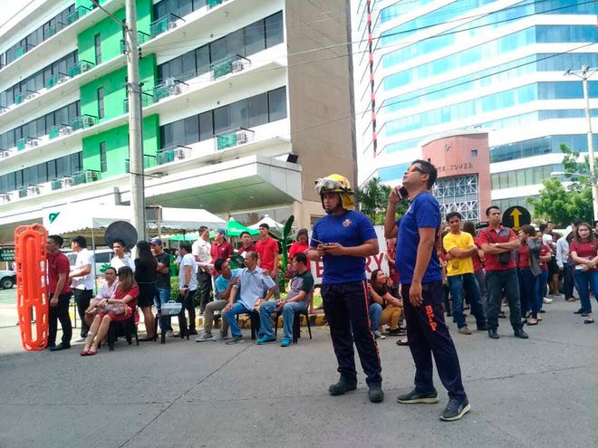 Office employees gather outside of buildings after a powerful earthquake was felt in Davao City, Philippines, on Tuesday.