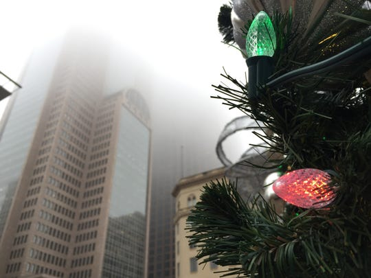 In this Dec. 19, 2018, file photo Christmas lights blink in the Main Street Garden Park as the Comerica Bank Tower disappears in a thick fog in downtown Dallas. Holiday staffing is one of a small business owner's biggest stressors. Even companies that aren't retailers or restaurants can have a year-end busy season, just when employees all want to take time off. (Irwin Thompson/The Dallas Morning News via AP, File)