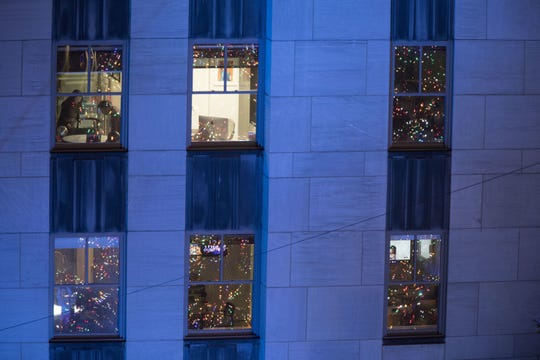 In this Nov. 28, 2018, file photo people work in their office after the Rockefeller Center Christmas tree is lit during the 86th annual Rockefeller Center Christmas tree lighting ceremony in New York. Holiday staffing is one of a small business owner's biggest stressors. Even companies that aren't retailers or restaurants can have a year-end busy season, just when employees all want to take time off. (AP Photo/Mary Altaffer, File)