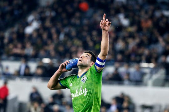 Seattle Sounders midfielder Nicolas Lodeiro celebrates his goal while holding his shoe during the first half of the team's MLS soccer Western Conference final against Los Angeles FC, Tuesday, Oct. 29, 2019, in Los Angeles.