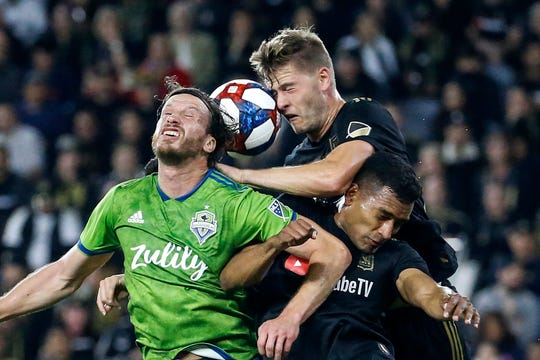 Seattle Sounders midfielder Gustav Svensson, left, vies for a head ball against Los Angeles FC defenders Walker Zimmerman, center, and Eddie Segura during the first half of the MLS soccer Western Conference final Tuesday, Oct. 29, 2019, in Los Angeles.