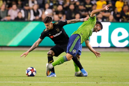 Los Angeles FC forward Brian Rodriguez, left, vies with Seattle Sounders midfielder Cristian Roldan for the ball during the first half of the MLS soccer Western Conference final, Tuesday, Oct. 29, 2019, in Los Angeles.
