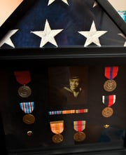 A shadowbox displays the late Alfonso Baes' Navy medals.