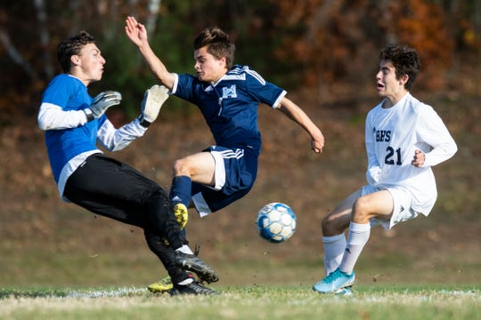 MMU's Will Hauf (7) collides with Burlington goalie Owen Harris (00) during the high school boys semifinal soccer game between the Burlington Seahorses and the Mount Mansfield Cougars at MMU High School on Tuesday afternoon October 29, 2019 in Jericho, Vermont.
