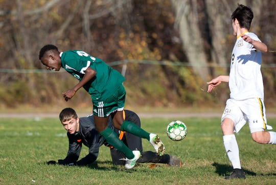 Green Mountain goalie Skyler Klezos, bottom, wins the ball away from Winooski's Yusfu Mami during a Division III boys soccer semifinal in Winooski on Tuesday, Oct. 29, 2019.