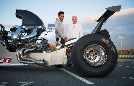 Travis Laster Jr., a senior member of the Seneca High School football team who drag races with his family up and down the East Coast, shows his dragster to Seneca High School football coach Bill Fisher.
