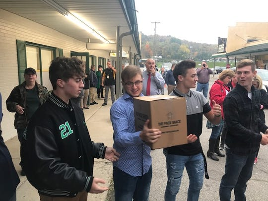 Huntington High School football players pass food along between the truck and service center.
