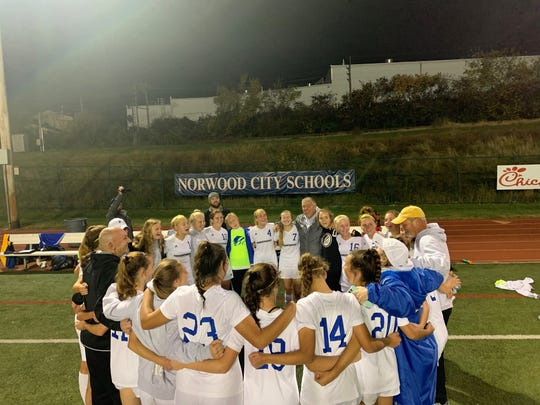 Mariemont girls soccer huddles around head coach Mike Haney after the Warriors beat Madeira, 2-1, Tuesday night in the D-III regional semifinals at Norwood's Shea Stadium.