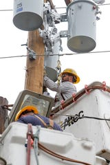 Lineman work to restore power for the transformers at Mark's Car Connection in Clarksville, Tenn., on Tuesday, Oct. 29, 2019.