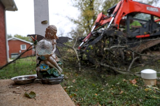 A small angel statue sits on the front deck of a home while workers clear yards of tree limbs brought down by a storm on Avalon Street in Clarksville, Tenn., on Tuesday, Oct. 29, 2019.