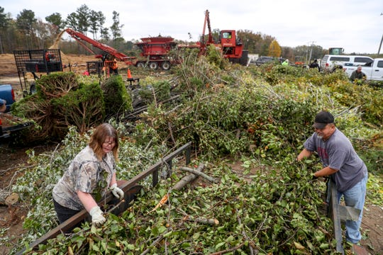 Henry Spade, right, and Tina Spade, left, pull off the limbs and tree remains they hauled from their yard to dispose of at Bi-County Solid Waste Management in Woodlawn, Tenn., on Tuesday, Oct. 29, 2019.