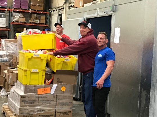 Workers and volunteers in the warehouse area at the Franklin Food Bank