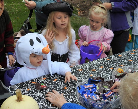 Nash Hoerig, 2, Jensen Bible, 6, and Kennedy Bible, 5, get candy at the Trail of Treats Tuesday at Clary Gardens.