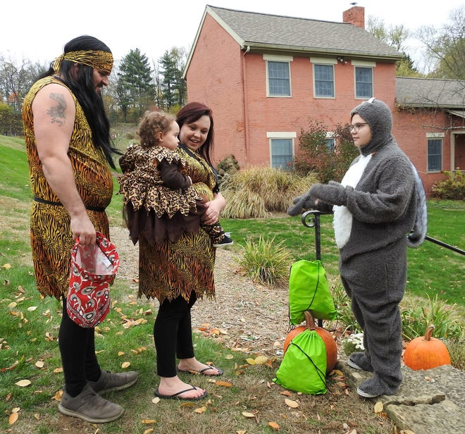 Shawn and Saundra Miller with their daughter Lucy, 2, dressed as cave people receive candy from Cheyenne Hutton dressed as a squirrel during the Trail of Treats Tuesday at Clary Gardens.