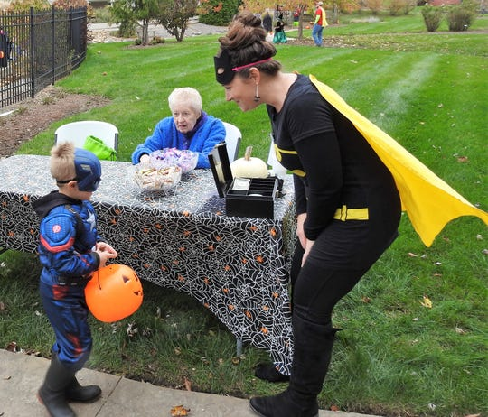 Gage Lowe, 4, as Captain America is greeted by Beth Clary and Jandi Adams as Batgirl at the Trail of Treats Tuesday at Clary Gardens.