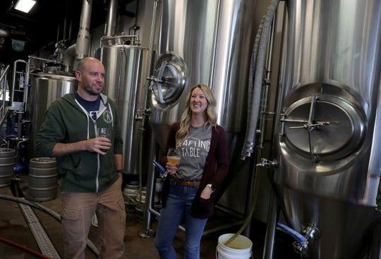 Aaron and Kristin Rzeznik, owners of Drafting Table Brewing Co., talk about their craft beers in the production room Wednesday, Oct. 23, 2019, in Wixom.