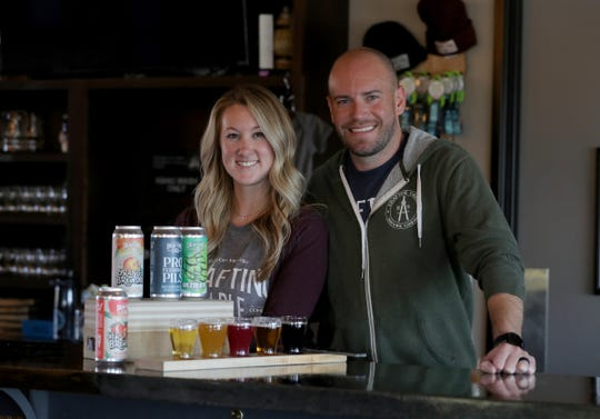 Aaron and Kristin Rzeznik, owners of Drafting Table Brewing Co., with a few of their craft beers Wednesday, Oct. 23, 2019, in Wixom.