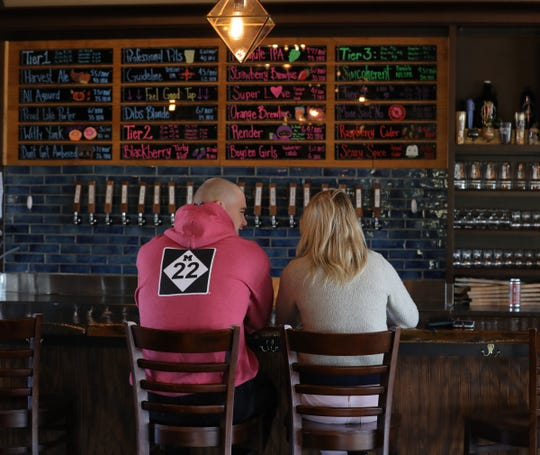 Cormac Littleton and Lauren Herremann from Wixom have a beer on Wednesday, Oct. 23, 2019, at Drafting Table Brewing Co. in Wixom.