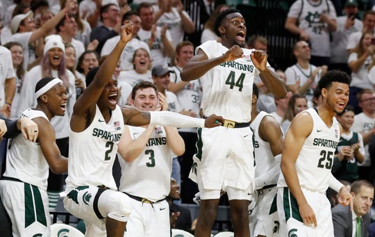 From left, Michigan State guards Cassius Winston (5), Rocket Watts Jr. (2), Foster Loyer (3), and forwards Gabe Brown (44) and Malik Hall (25) react on the bench as guard Steven Izzo scores his first point on a free throw during the second half of MSU's 85-50 exhibition win on Tuesday, Oct. 29, 2019, in East Lansing.