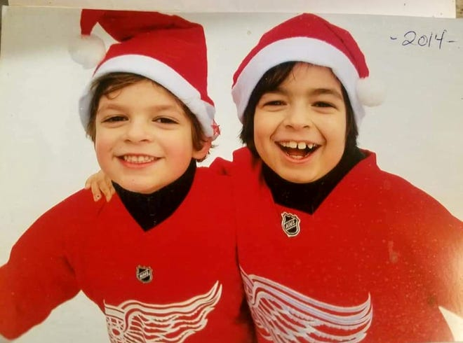 Grosse Pointe brothers Logan and Briggs Connolly, both hockey players, smile for the camera in their Red Wings gear in this 2014 photo. The boys, ages 9 and 11, died in a house fire Monday.