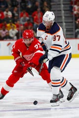Detroit Red Wings center Dylan Larkin (71) and Edmonton Oilers center Connor McDavid (97) battle for the puck in the second period of an NHL hockey game, Tuesday, Oct. 29, 2019, in Detroit.
