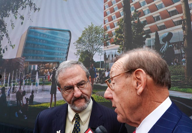 Mark Schlissel, left, president of the University of Michigan, and philanthropist Stephen Ross speak to the news media following a news conference on Wednesday, Oct. 30, 2019, for the announcement of the new $300 million U-M Detroit Center for Innovation on the 14-acre site of the abandoned Wayne County Jail project in Detroit.
