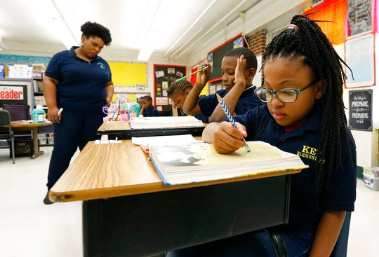 In this April 18, 2019 file photo, Elize'a Scott, a Key Elementary School third grade student, right, reads under the watchful eyes of teacher Crystal McKinnis, left in Jackson, Miss. Nationally, lower-performing students are doing worse in math and reading, thus dragging down overall results on the Nation's Report Card.