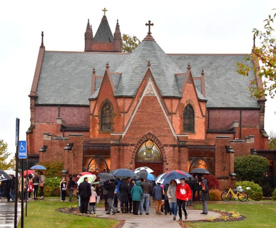 With the church at capacity, some mourners stand outside in the rain at St. Paul on The Lake in Grosse Pointe Farms  Wednesday evening for the service in memory of fire victims Briggs and Logan Connolly.