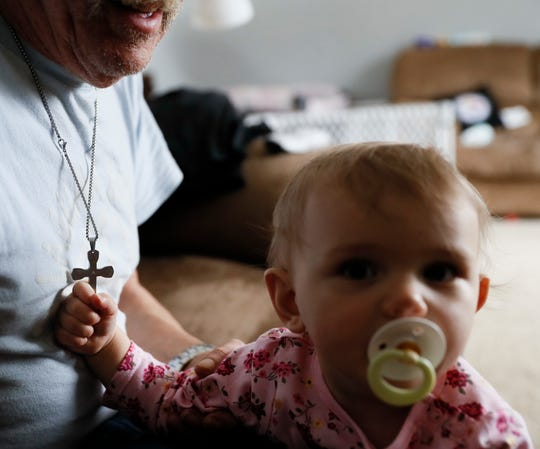 In this Nov. 28, 2018, file photo Annabella Wolikow, 10-month-old daughter of Tom Wolikow, holds her grandfather John's crucifix necklace at their home in Warren, Ohio.