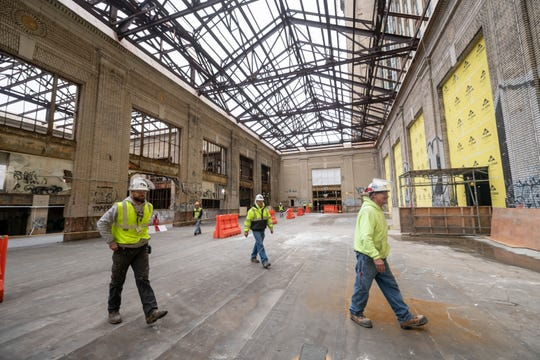 Workers walk through the atrium inside the Michigan Central Depot.