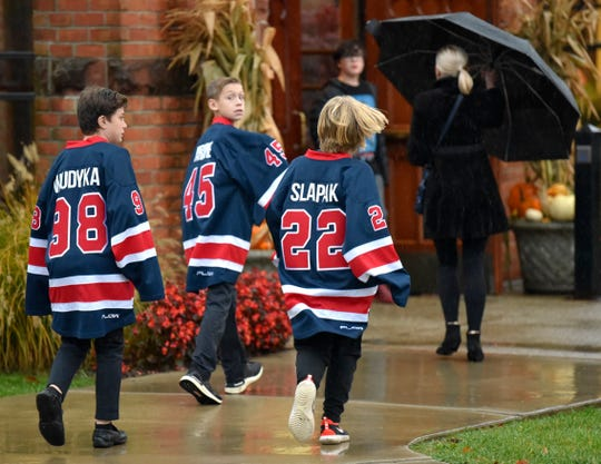 Three boys, wearing hockey jerseys, prepare to enter St. Paul on The Lake in Grosse Pointe Farms  for the service in memory of two boys, Briggs and Logan Connolly, who died in a house fire Monday at their Grosse Pointe home.