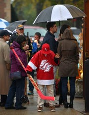 St. Clair Shores Hockey Association 07 Black Team goalie Adin Chaddha, 12, of Grosse Pointe Park, briefly practices his moves as he and other mourners stand outside in the rain after the fire marshal declares the church and overflow room are at capacity.