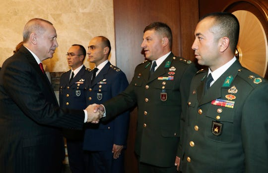 Turkish President Recep Tayyip Erdogan speaks with Turkish army officers who has participated in Syria operation, during a Republic Day reception, in Ankara, Turkey, Tuesday, Oct. 29, 2019.