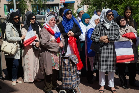FILE - In this May 16, 2014 file photo, women wear muslim scarf and hold French flags gather outside the town hall of Mantes la Ville, northwest of Paris.