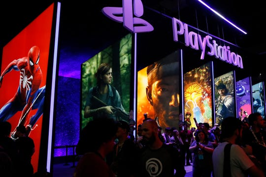 FILE - In this June 14, 2018, file people stand online next to the PlayStation booth at the 24th Electronic Entertainment Expo E3 at the Los Angeles Convention Center.