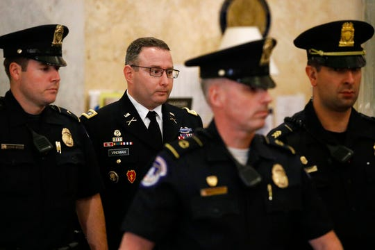Army Lt. Col. Alexander Vindman, second from left, a military officer at the National Security Council, departs a closed door meeting after testifying as part of the House impeachment inquiry into President Donald Trump, Tuesday, Oct. 29, 2019, on Capitol Hill in Washington.